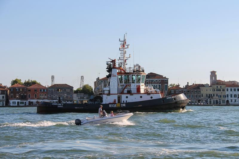 Шлюпка и моторная лодка гужа Angelina c с людьми в лагуне Венеции, стоковое фото