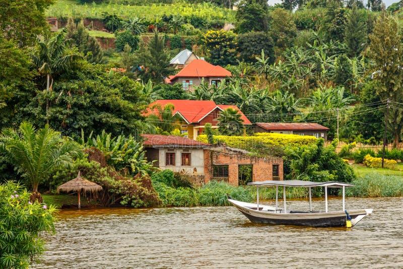 Шлюпка крыши поставленная на якорь на побережье с руандийской деревней на заднем плане, озеро Kivu, Руанда стоковое изображение rf