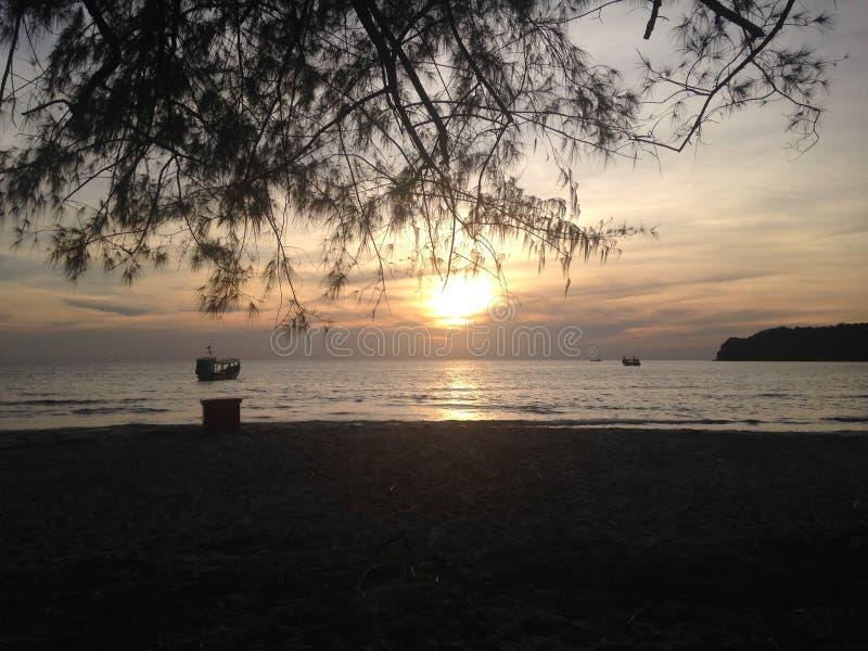 Шлюпка на море на предпосылке захода солнца Взгляд от берега стоковое фото