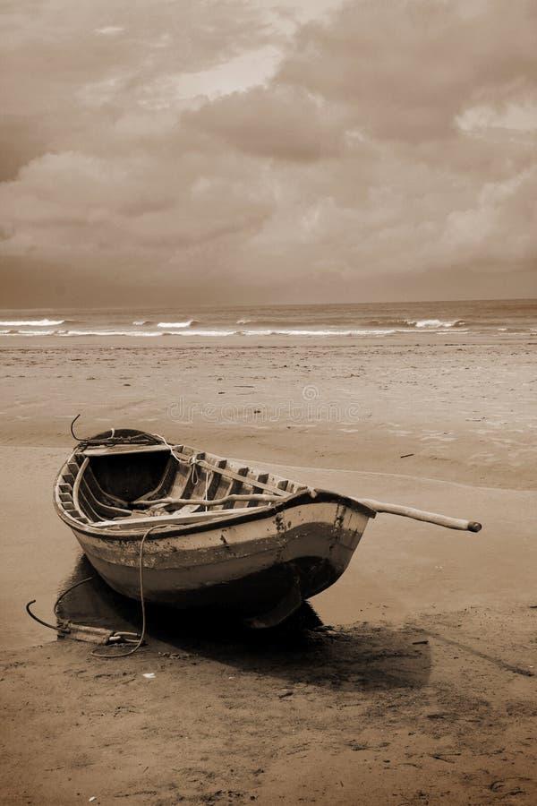 Шлюпка на пляже в sepia стоковое изображение