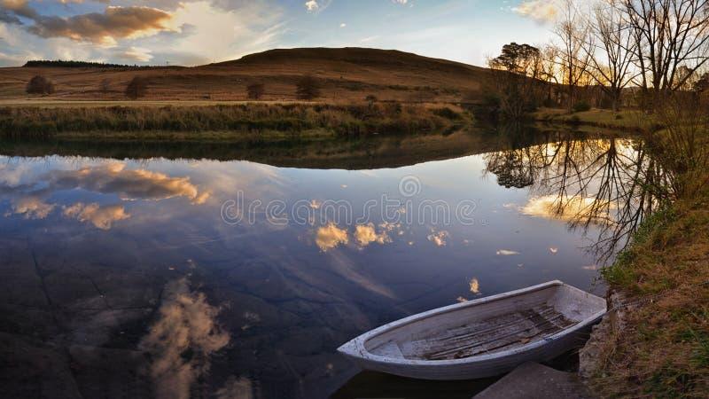 Шлюпка на реке на заходе солнца стоковые изображения