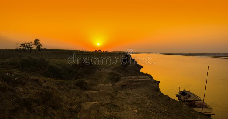 Шлюпка на речном береге на времени захода солнца стоковая фотография rf