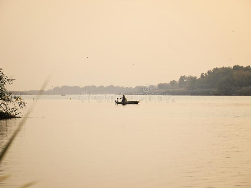 Шлюпка на спокойном озере с рыболовом и тростником на восходе солнца стоковое изображение