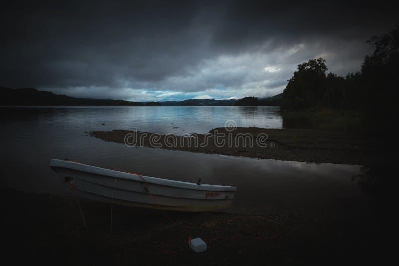 Шлюпка озером Jonsvatnet берега озера, Норвегией стоковые изображения