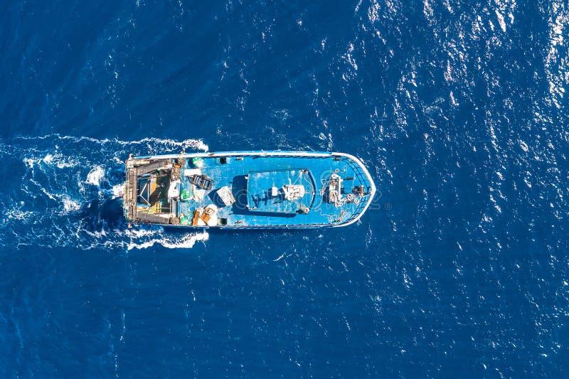 Шлюпка плавая в голубое море, вид с воздуха рыболовецкого судна сверху стоковое фото rf