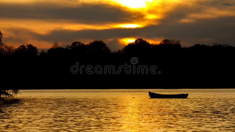 Шлюпка плавая на озеро на сумраке стоковые фото