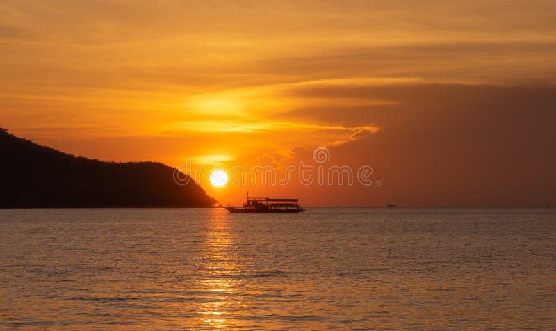 Шлюпка рыболова силуэта плавая на море во время золотого захода солнца с солнцем отражает на воде стоковая фотография rf