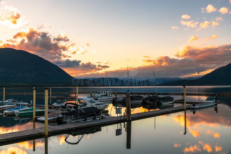 Шлюпки в гавани на озере окруженном красивыми горами на заходе солнца стоковое фото