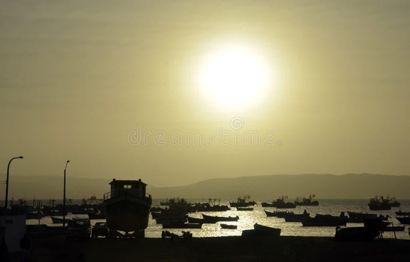 шлюпки залива удя полное заходящее солнце стоковое фото rf