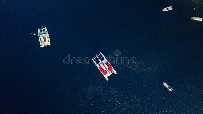 Шлюпки и катамараны в темносиней воде, Santorini, Греции стоковые изображения rf