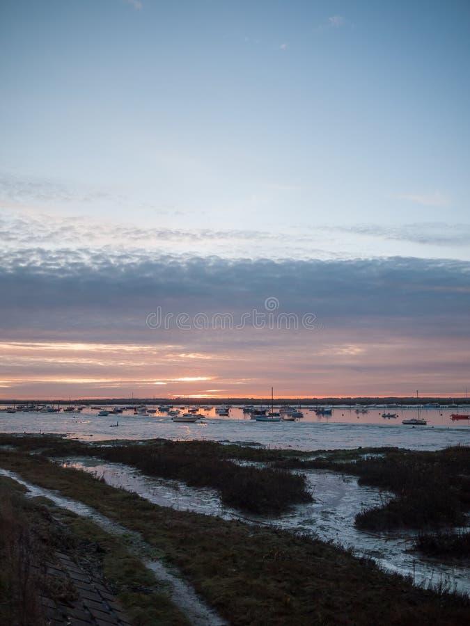 Шлюпки Марины гавани пляжа берега моря облаков установленного неба Солнця драматические стоковая фотография