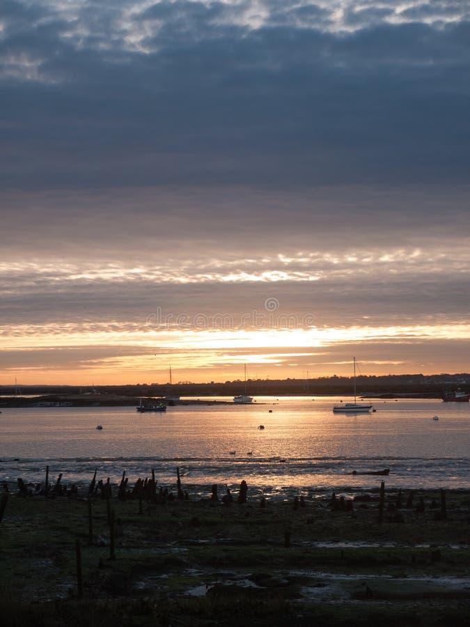 Шлюпки Марины гавани пляжа берега моря облаков установленного неба Солнця драматические стоковое изображение