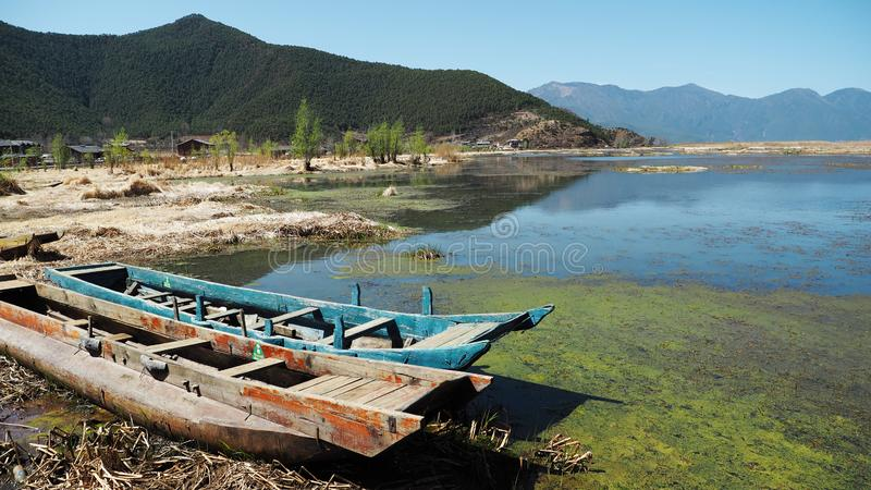 Шлюпки мелким берегом озера Lugu стоковое фото rf