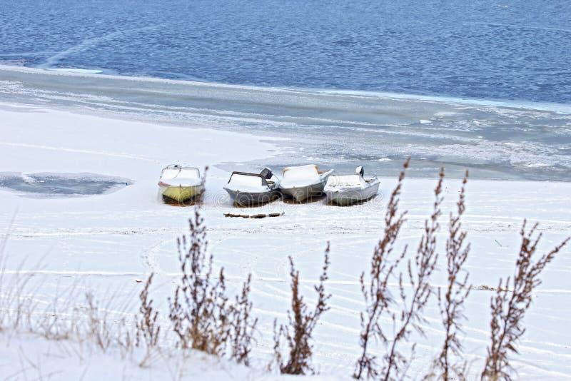 Шлюпки на покрытом снег береге стоковые изображения rf