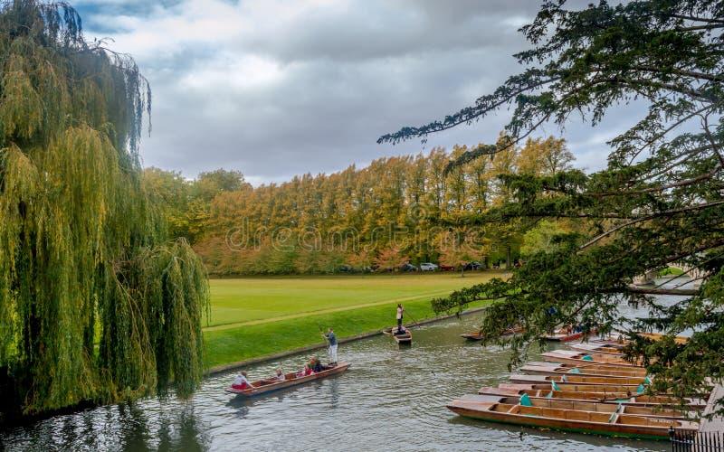 Шлюпки припаркованные в ряд и люди наслаждаясь бить на кулачке реки во время лета на Кембридже стоковые фото