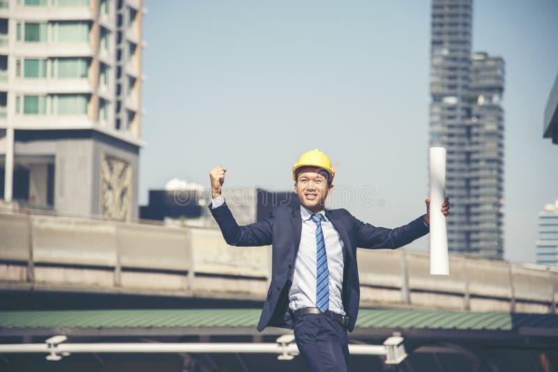 Шляпа желтого шлема носки инженера успеха трудная для защитить для того чтобы возглавить на месте конструкцию для безопасности o стоковые фото