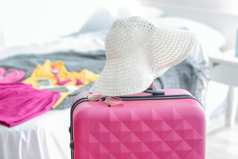 Шляпа и солнечные очки пляжа на чемодане перемещения внутри помещения стоковые изображения rf