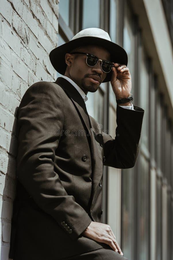 Шляпа и солнечные очки fedora модного Афро-американского бизнесмена нося представляя путем построение стоковое фото