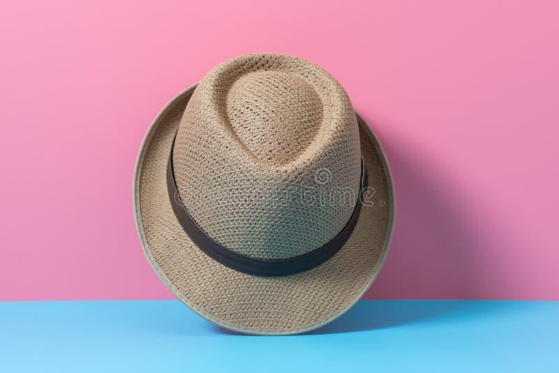 Шляпа моды людей на голубой и розовой бумаге, минимальном backgroun стиля стоковая фотография