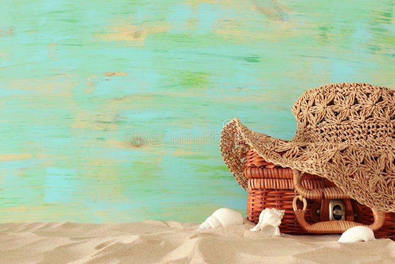 Шляпа моды пляжа женская над чемоданом соломы в песке Тропическая концепция летних каникулов стоковая фотография