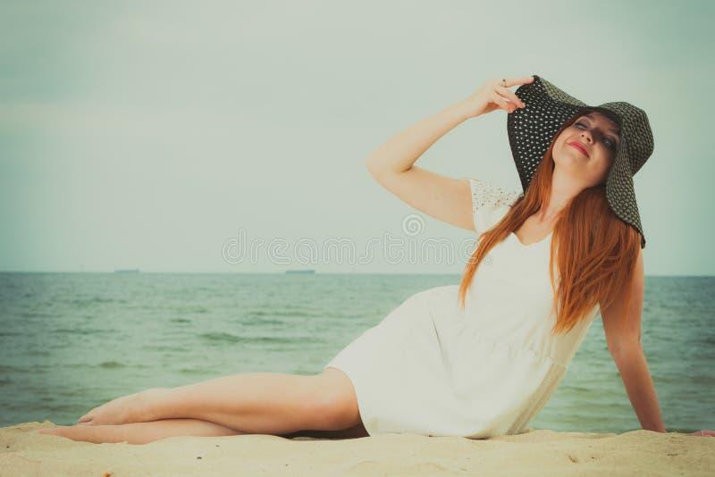 Шляпа солнца женщины Redhead нося лежа на пляже стоковое фото rf