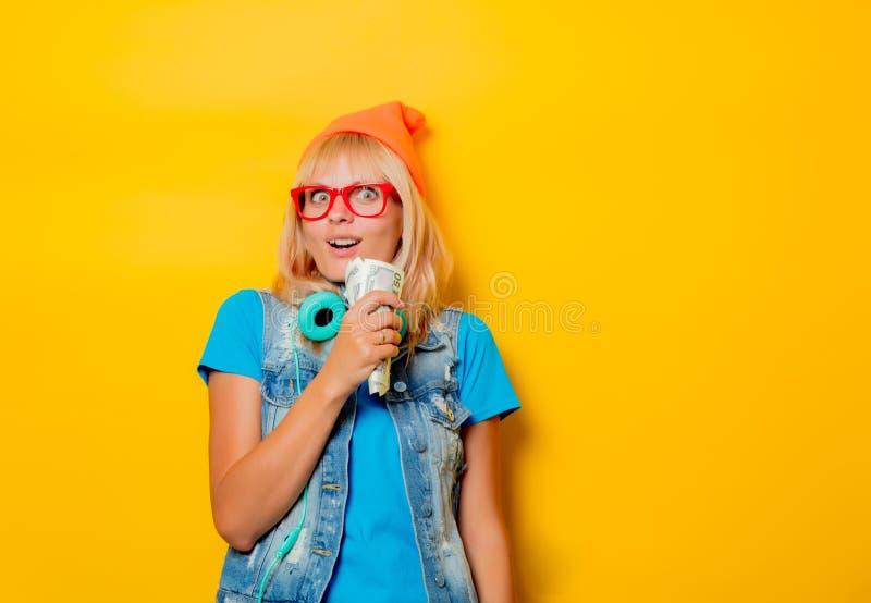 Шляпа ультрамодной девушки оранжевая с деньгами стоковое изображение