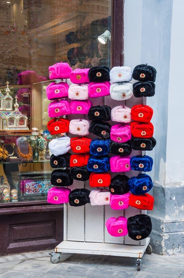 Шляпы сувенира с щитками уха других цветов с советскими кокардами на улице стоят перед окном сувенирного магазина на Ni стоковое фото