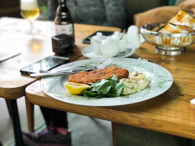 Шницель цыпленка с салатом и лимоном картошки служил на ресторане стоковые изображения
