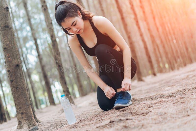 Шнурок женщины sporty в лесе после бегуна стоковое изображение