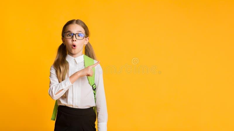 Шокированная школьница, указывающая пальцем на желтый фон, Панорама стоковое изображение