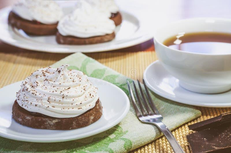 Шоколадные торты со сливк яйца белой, чашкой горячего чая, частями шоколада и вилкой на деревянном столе стоковые фото