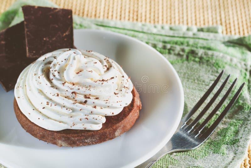 Шоколадный торт со сливк яйца белой, части шоколада и вилка на деревянном столе стоковая фотография