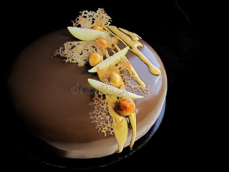 Шоколадный торт Яблока и карамельки ореховый на черной предпосылке стоковое фото rf