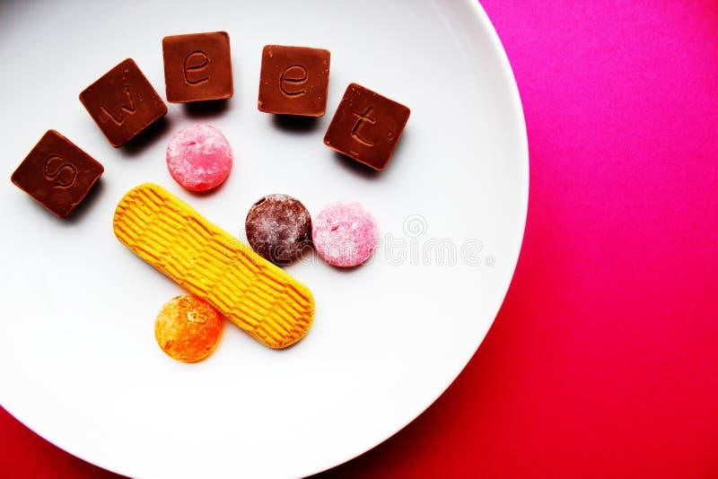 Шоколады и леденцы на палочке на белой плите стоковая фотография rf