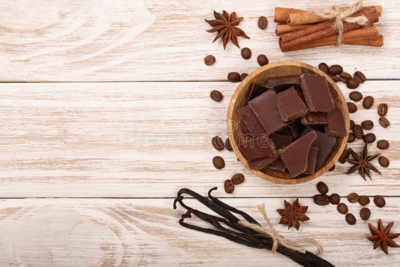 Шоколад, ванильные ручки, циннамон, кофейные зерна на белой деревянной предпосылке с космосом экземпляра для вашего текста Взгляд стоковые изображения
