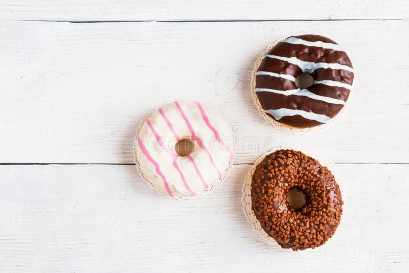 Шоколад и застекленные donuts, пинк, белизна, коричневая на деревянном столе, взгляд сверху стоковые изображения