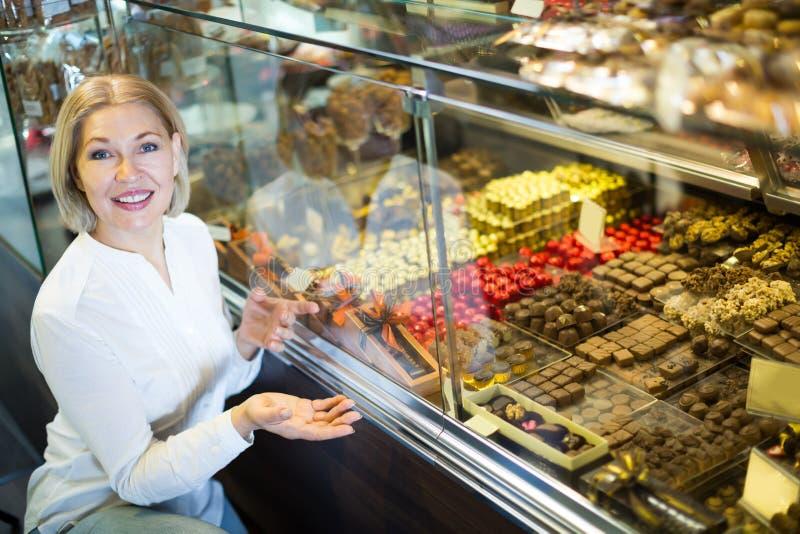 Шоколад счастливого белокурого пенсионера покупая стоковое изображение rf