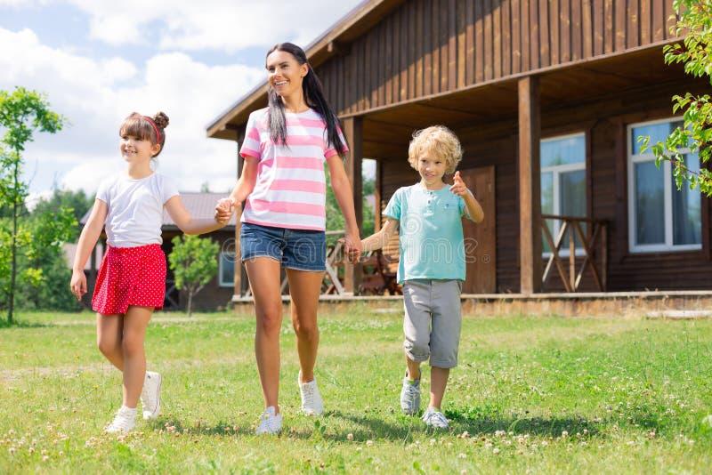 Шорты джинсовой ткани матери нося принимая ее детей для прогулки стоковое фото rf