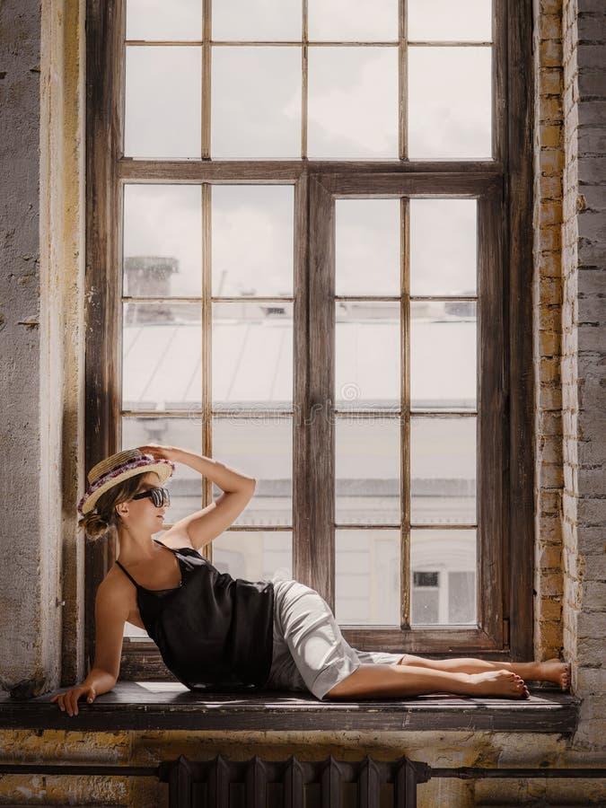 Шорты молодой женщины нося белые, черная верхняя часть, шляпа и солнечные очки стоковые изображения rf