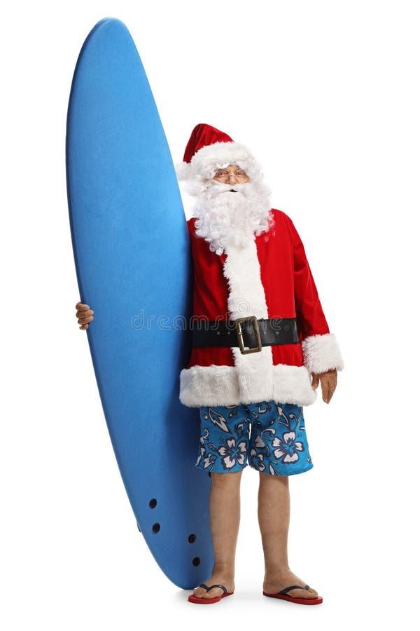 Шорты Санта Клауса нося плавая и удержание доски серфинга стоковые изображения rf