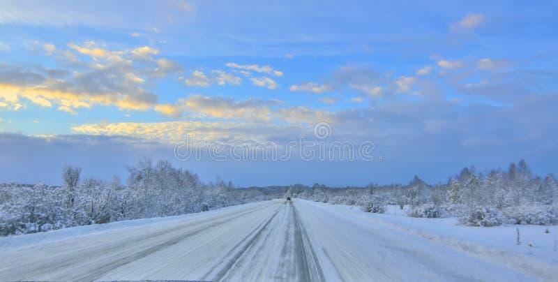 Шоссе зимы снежное на сумерках захода солнца запачканное от привода скорости высоты стоковая фотография rf