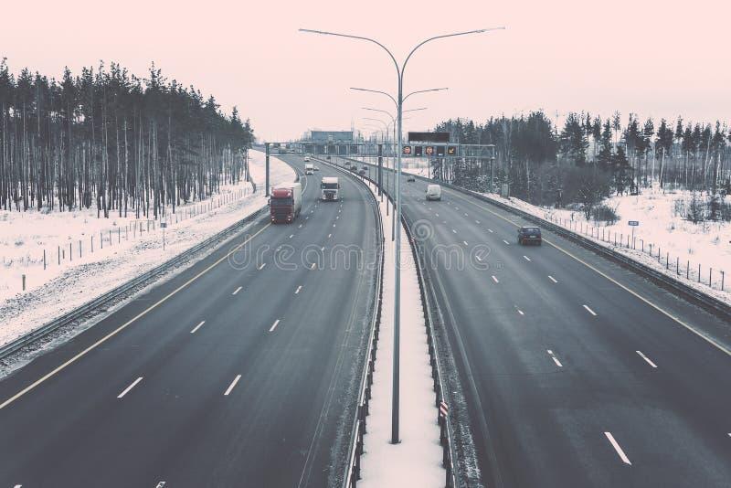 Шоссе зимы с тележками и автомобилями среди тонизированного стиля леса зимы винтажного стоковые фотографии rf