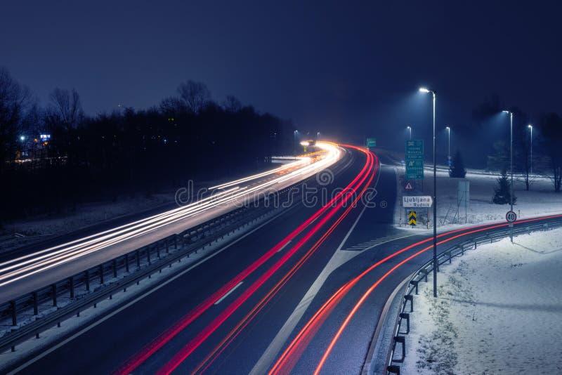 Шоссе снежной ночью со следами света от входящего и исходящего движения стоковые изображения rf