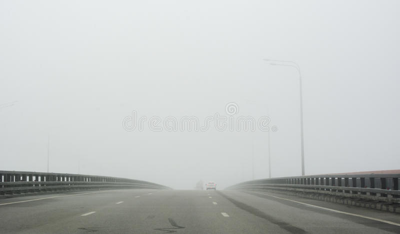 Шоссе через мост в тумане стоковая фотография