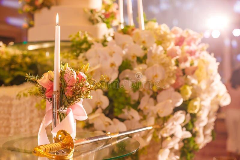 Шпага вырезывания подсвечника и свадебного пирога на стеклянном столе рядом с этапом в свадебной церемонии Концепция инструмента  стоковое изображение rf