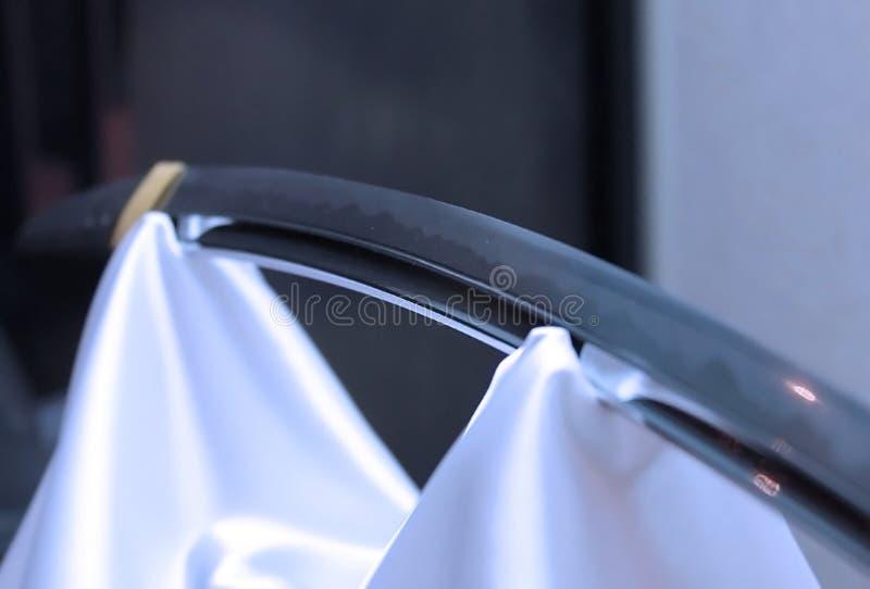 Шпага самураев лезвия японская на белом silk drapery стоковые изображения rf