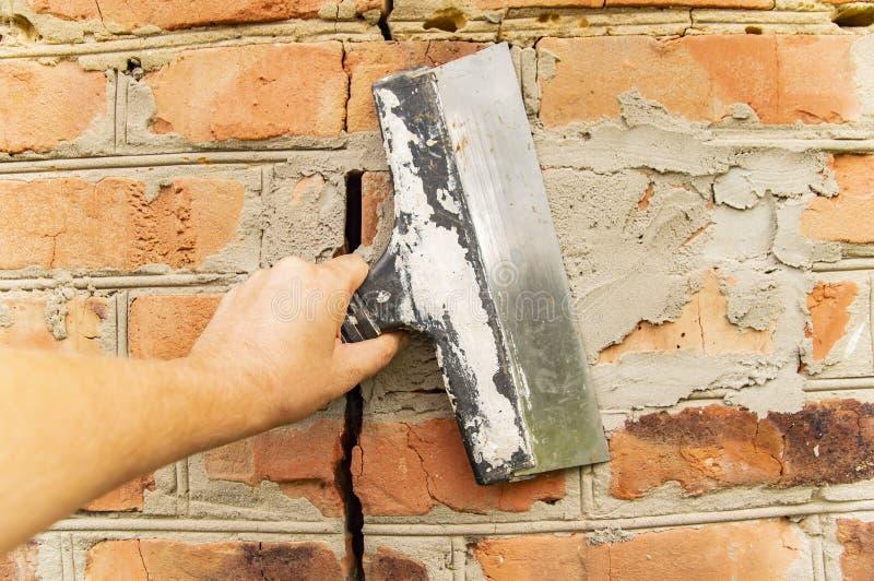 Шпатель в руке построителя - ремонте кирпичной стены стоковое изображение