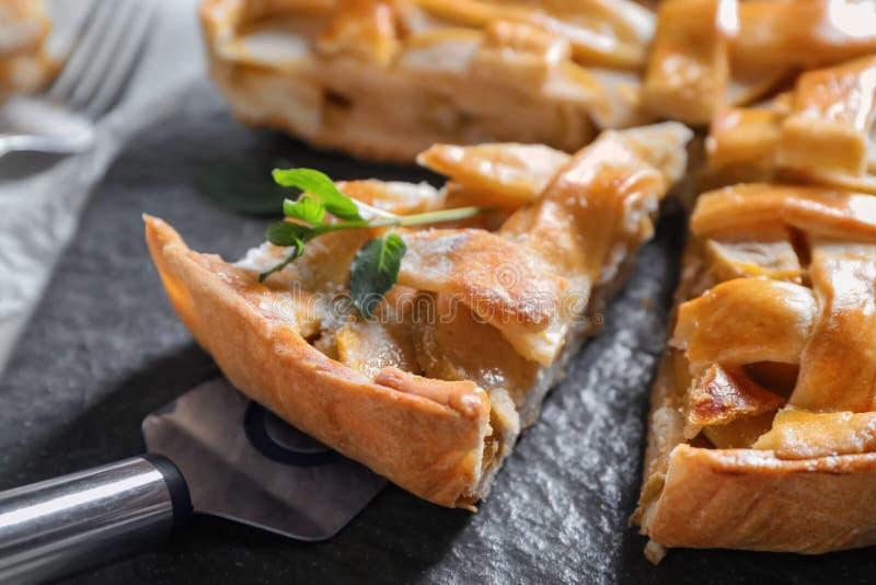 Шпатель и часть вкусного яблочного пирога на плите шифера, крупном плане стоковые изображения