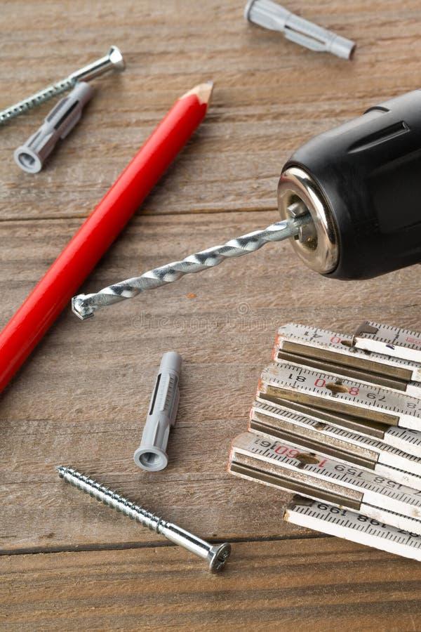Шпонка штепсельной вилки стены с винтом, сверлом электричества, брусом для кантовки листов и карандашем на деревянном столе стоковое фото