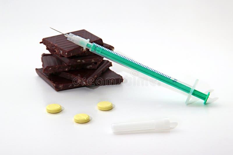 Шприц инсулина, темный горький шоколад и желтые таблетки на белом конце предпосылки вверх Шоколад концепции диабетический или стоковые фото